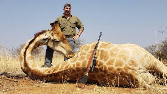 Idaho Fish and Game commissioner Blake Fischer poses with a giraffe in Namibia.