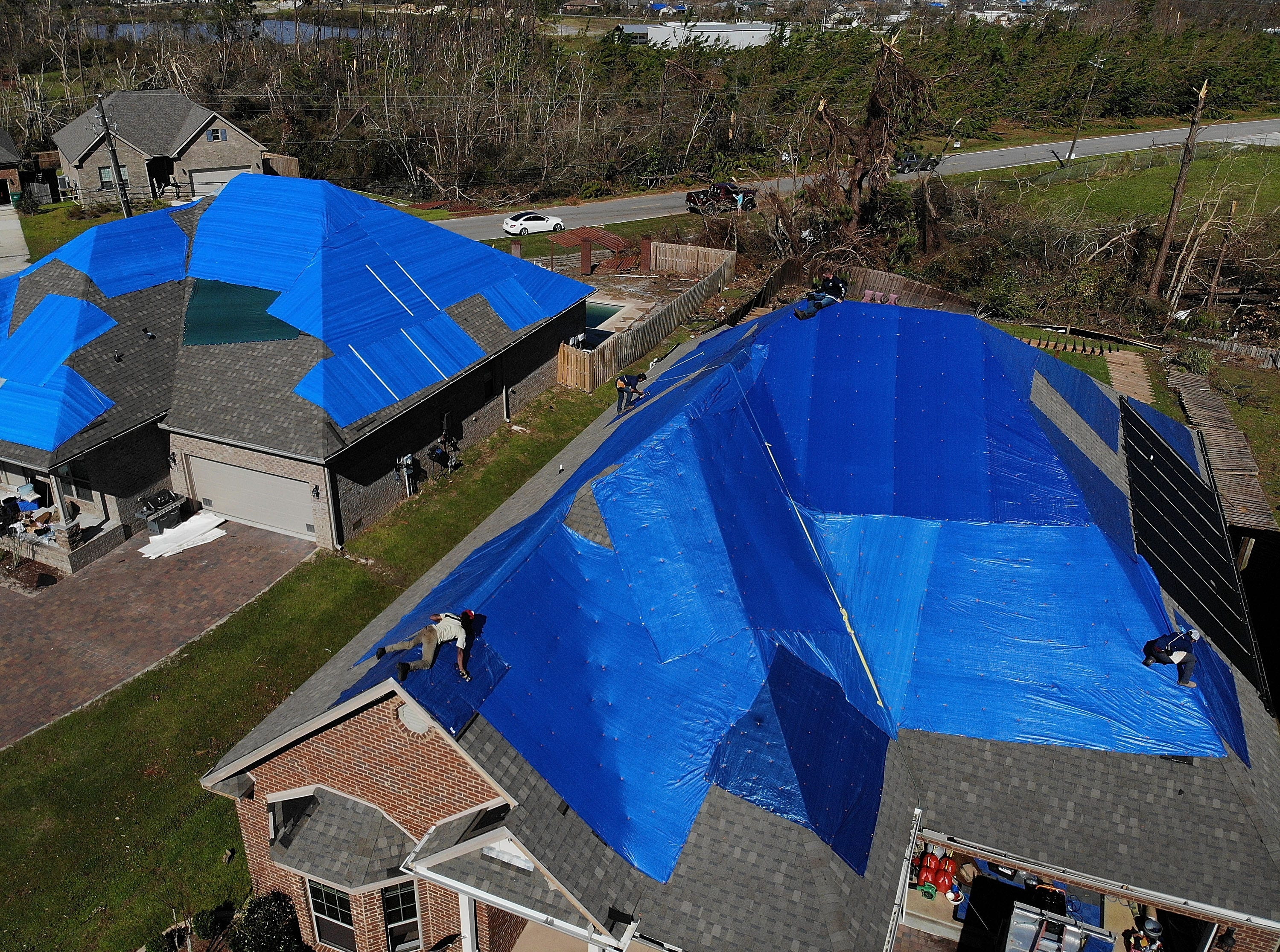 Workers from Total Quality Restoration place a tarp on a damaged roof as people start the process of rebuilding after Hurricane Michael on Oct. 16, 2018 in Panama City, Fla.