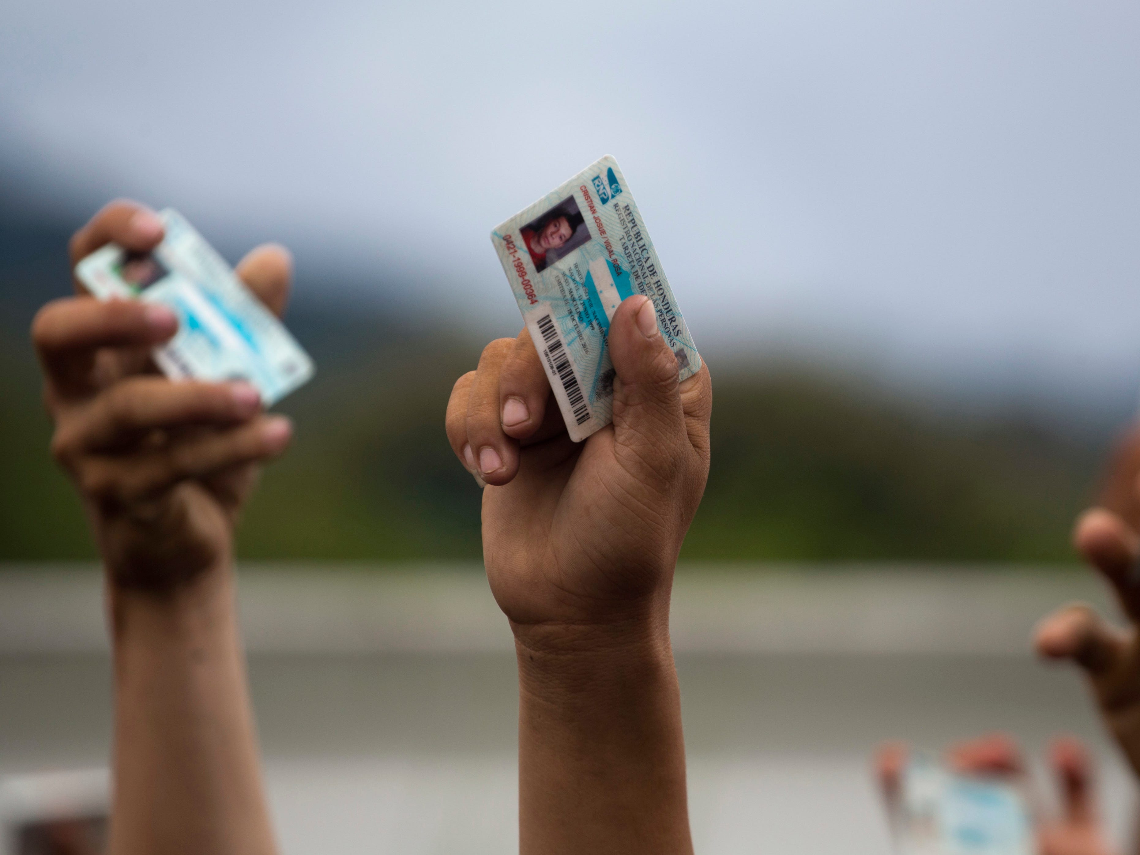 Honduran migrants holds up their national ID cards as Guatemalan police block them and their caravan after the group crossed the Honduras-Guatemala border without incident, in Esquipulas, Guatemala, Monday, Oct. 15, 2018. Police stopped the migrants for several hours but the travelers refused to return to the border and were eventually allowed to pass.  (AP Photo/Moises Castillo) ORG XMIT: XMC131