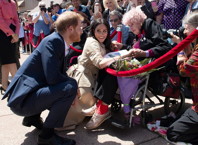 Britain's Prince Harry and Meghan, Duchess of Sussex meet 98-year-old Daphne Dunne outside the Opera House in Sydney, Australia, Tuesday, Oct. 16, 2018.