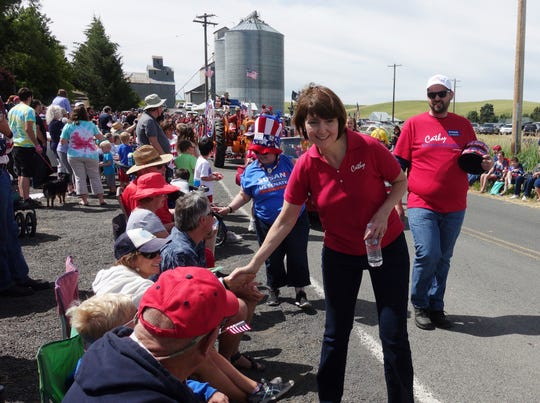 Rep. Cathy McMorris Rodgers, R-Wash., shakes hands as she walks in the 2018 Fourth of July Parade in Johnson, Wash.