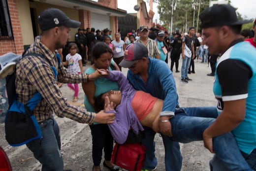 A faint Honduran migrant woman is helped as Guatemalan police temporarily block the road after her caravan crossed the Honduras-Guatemala border without incident, in Esquipulas, Guatemala, Monday, Oct. 15, 2018. Police stopped the migrants for several hours but the travelers refused to return to the border and were eventually allowed to pass. (AP Photo/Moises Castillo) ORG XMIT: XMC136