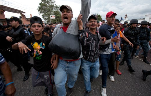 Honduran migrants walk past a roadblock of Guatemalan police as they make their way to the U.S., in Esquipulas, Guatemala, Monday, Oct. 15, 2018. Police stopped the migrants for several hours but the travelers refused to return to the border and were eventually allowed to pass. (AP Photo/Moises Castillo) ORG XMIT: XMC134