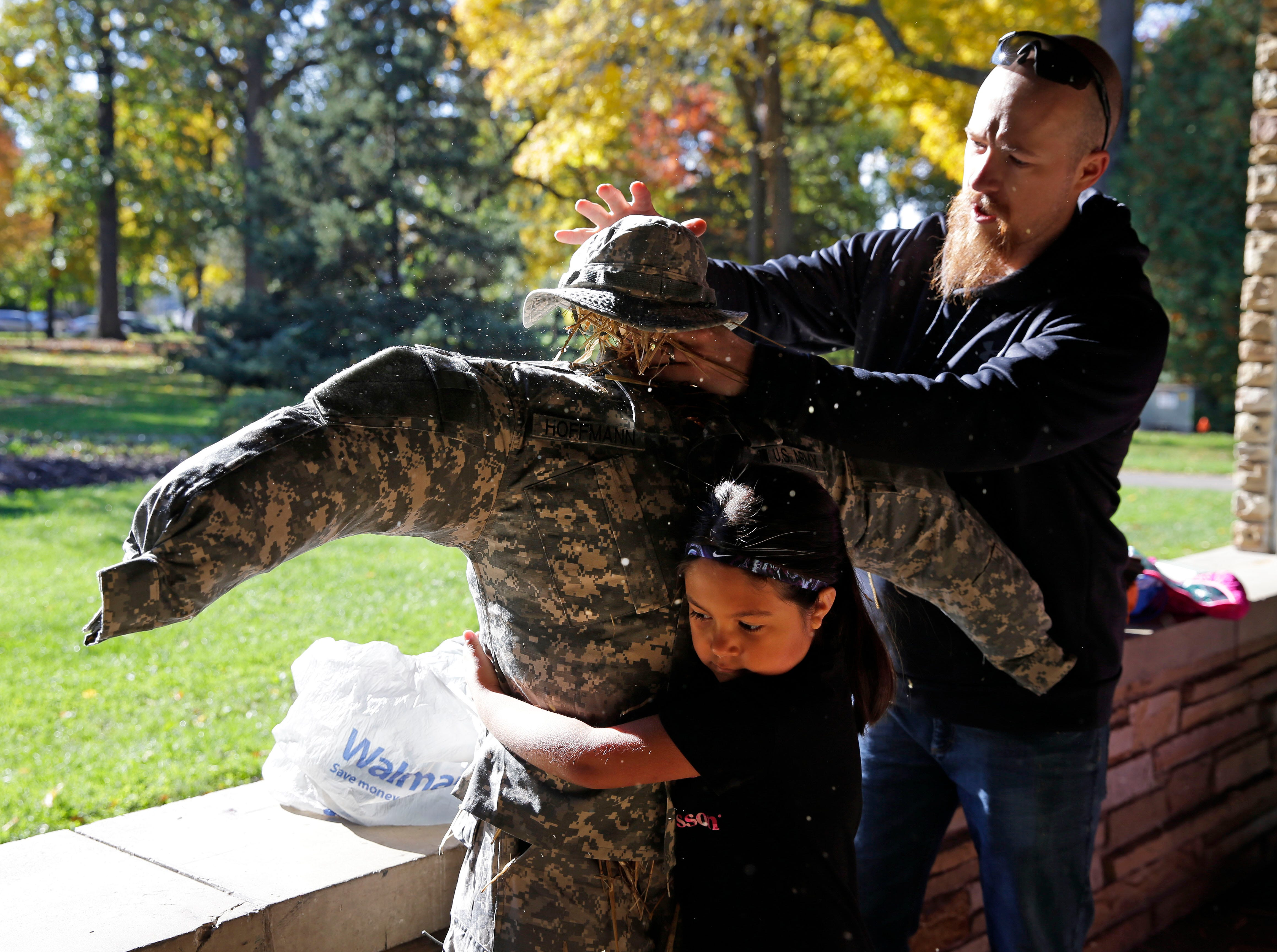 Devin Hoffmann and his daughter Gabby work on their scarecrow during the annual Build-A-Scarecrow event. The Neenah Parks and Recreation Department provided the frame and straw and families brought clothes and imaginations Saturday, October 13, 2018, at Riverside Park in Neenah, Wis.