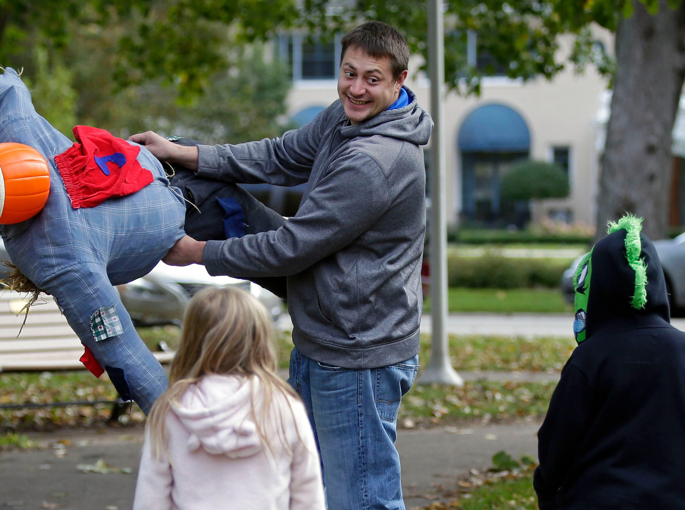 Roland Kessen flies a scarecrow around as Hailey, left, and Isaac Kessen watch, at the annual Build-A-Scarecrow event. The Neenah Parks and Recreation Department provided the frame and straw Saturday, October 13, 2018, at Riverside Park in Neenah, Wis.