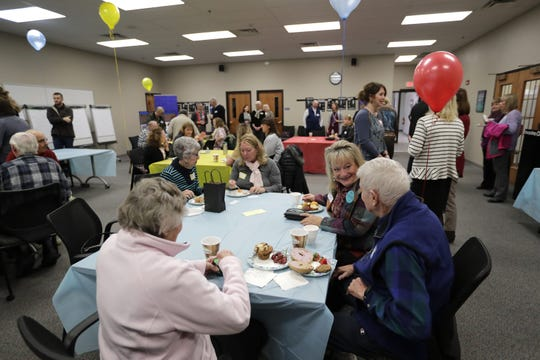 People gather Wednesday at the Goodwill campus in Menasha as the Fox Valley Memory Project shows off new office space and unveils a new logo.