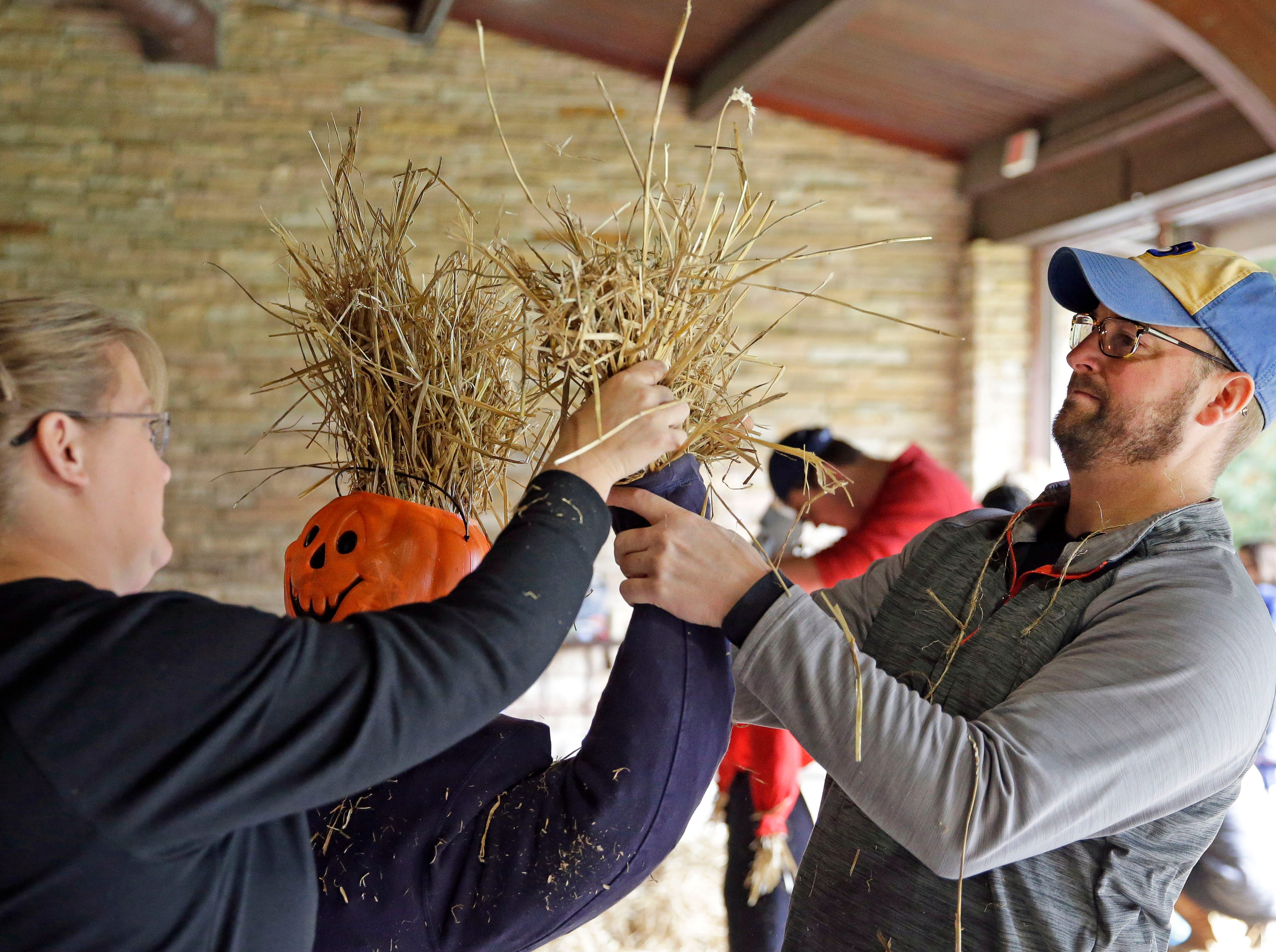 Val and Pete Splittgerber work on a scarecrow as the Neenah Parks and Recreation provided the frame and the straw for the annual Build-A-Scarecrow event Saturday, October 13, 2018, at Riverside Park in Neenah, Wis.