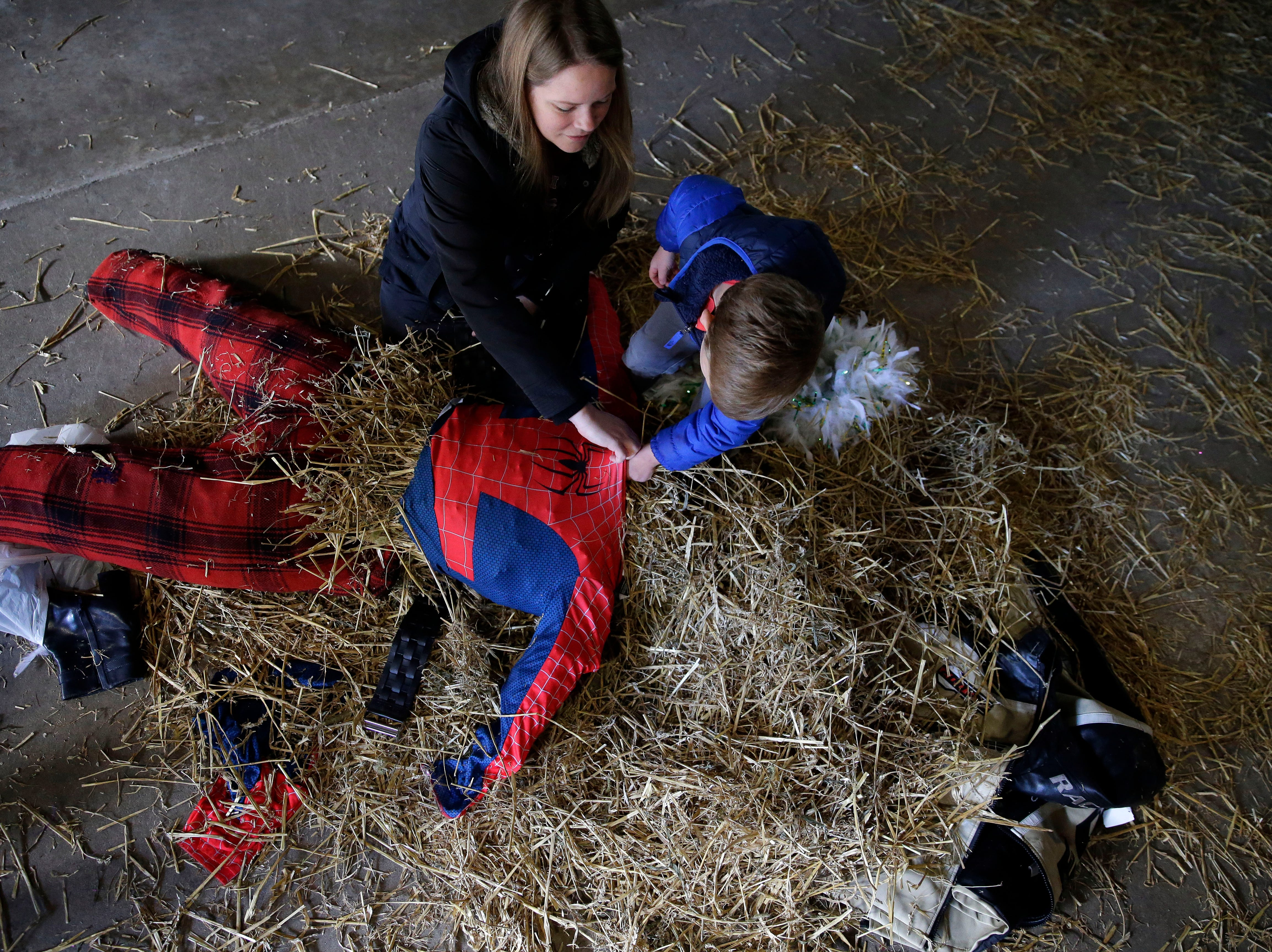 Tiffany and Stuart Wilson work on a scarecrow as the Neenah Parks and Recreation provided the frame and the straw for the annual Build-A-Scarecrow event Saturday, October 13, 2018, at Riverside Park in Neenah, Wis.