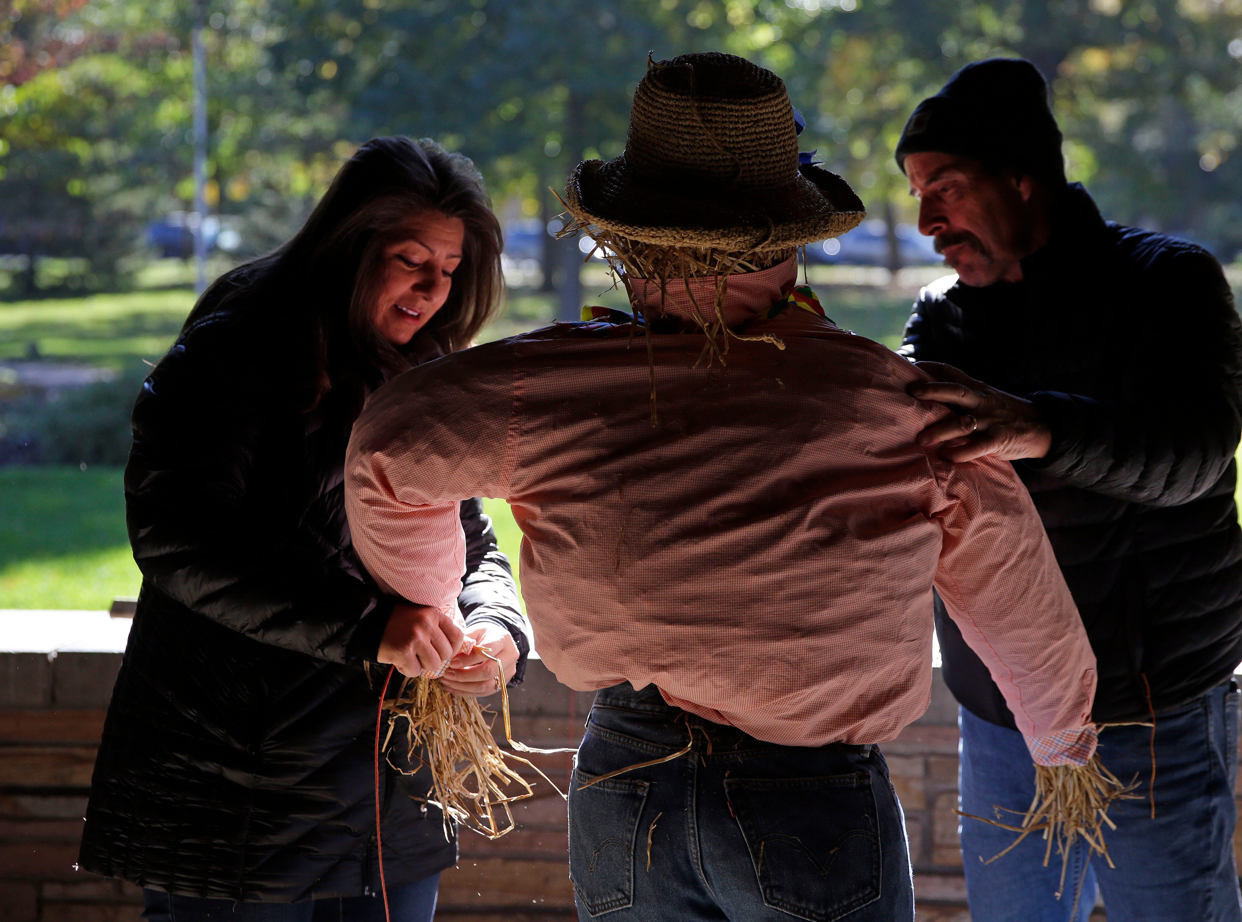 Consuelo Rodriguez and Dale Ables work on a scarecrow as the Neenah Parks and Recreation provided the frame and the straw for the annual Build-A-Scarecrow event Saturday, October 13, 2018, at Riverside Park in Neenah, Wis.