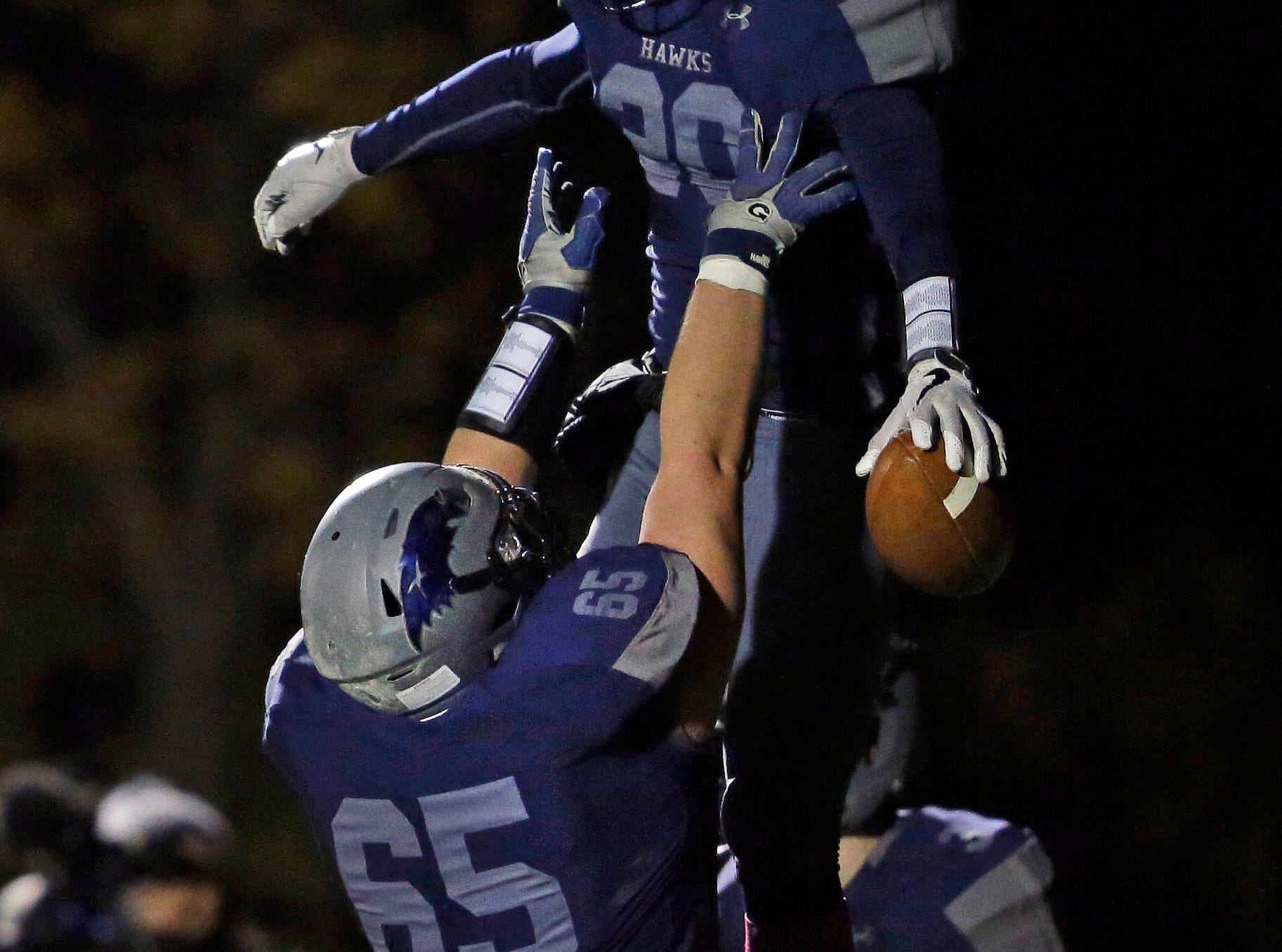 TJ Van Eperen (20) of Xavier celebrates a touchdown with Eli Blohowiak as the Hawks take on Waupaca in a Bay Conference football game Friday, October 12, 2018, at Rocky Bleier Field in Appleton, Wis.