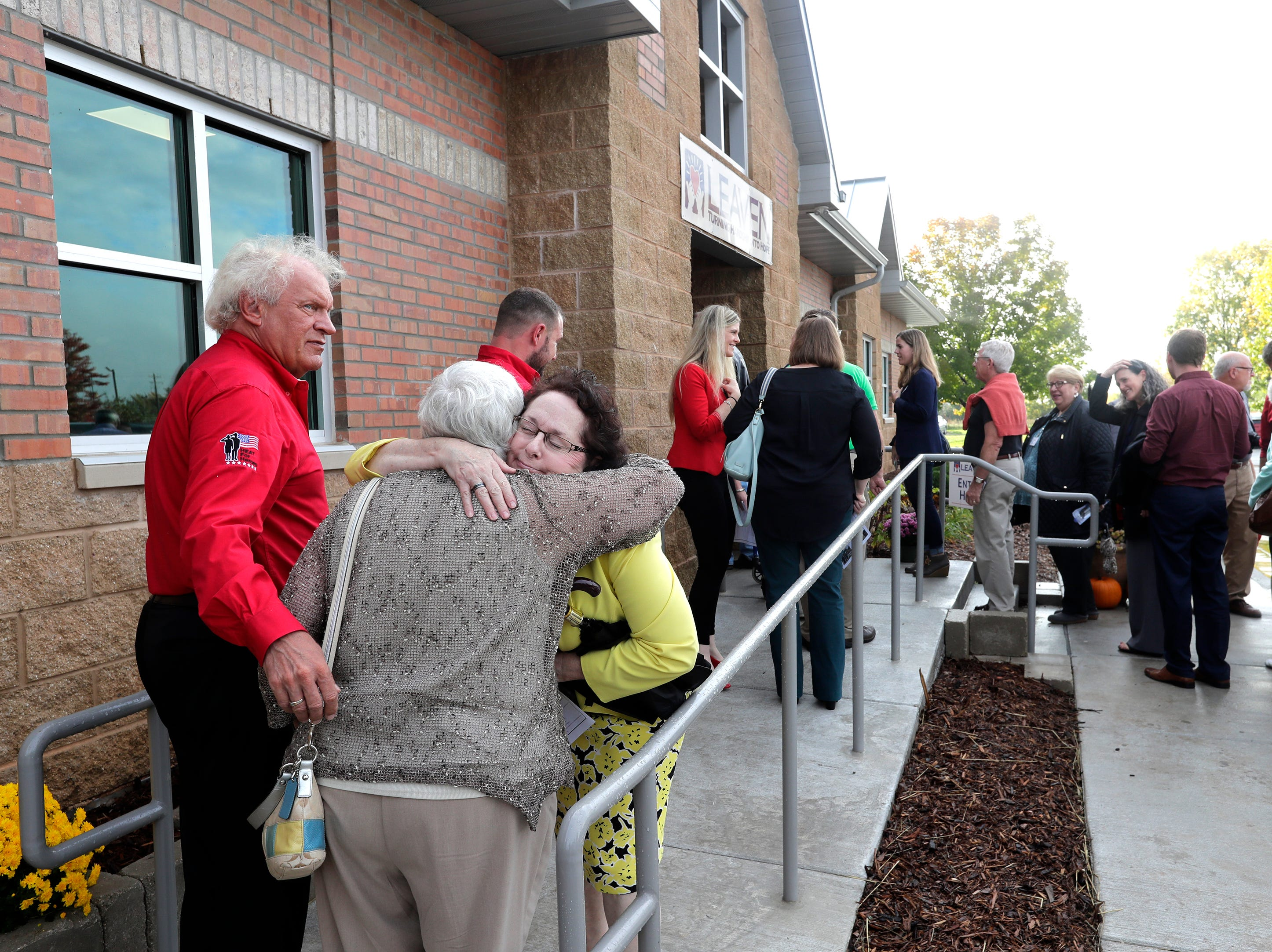 Attendees line up for a tour following a ribbon cutting event for the grand opening of the new LEAVEN Community Resource Center Wednesday, Oct. 10, 2018, in Menasha, Wis. LEAVEN or Limited Emergency Assistance Valley Ecumenical Network provides emergency financial assistance to people in need.