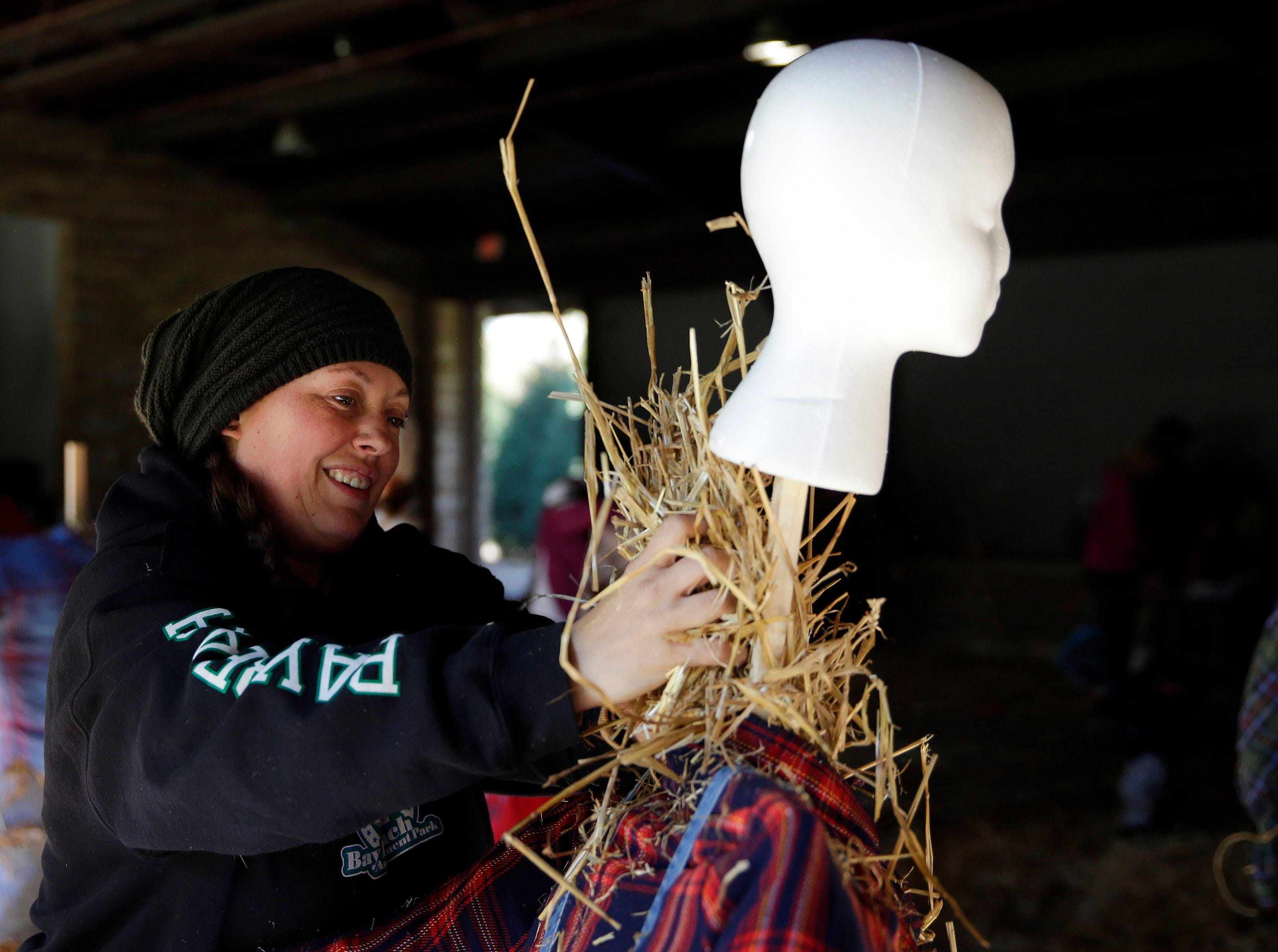 Rhiannon Gauerke works on a scarecrow as the Neenah Parks and Recreation provided the frame and the straw for the annual Build-A-Scarecrow event Saturday, October 13, 2018, at Riverside Park in Neenah, Wis.