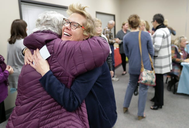 Fox Valley Memory Project Jill Grambow, right, hugs a friend and former coworker, Sue Borree, as the organization unveils a new logo and new office space on Wednesday at the Goodwill campus in Menasha.