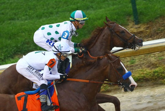 Mike Smith aboard Justify (7) races Corey J. Lanerie aboard Promises Fulfilled (3) during the 144th running of the Kentucky Derby at Churchill Downs.