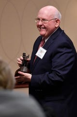 Larry Wolz takes his award back to his seat after being named outstanding volunteer during the 2018 Abilene Art Awards at the Celebrate the Arts in Abilene luncheon Wednesday.