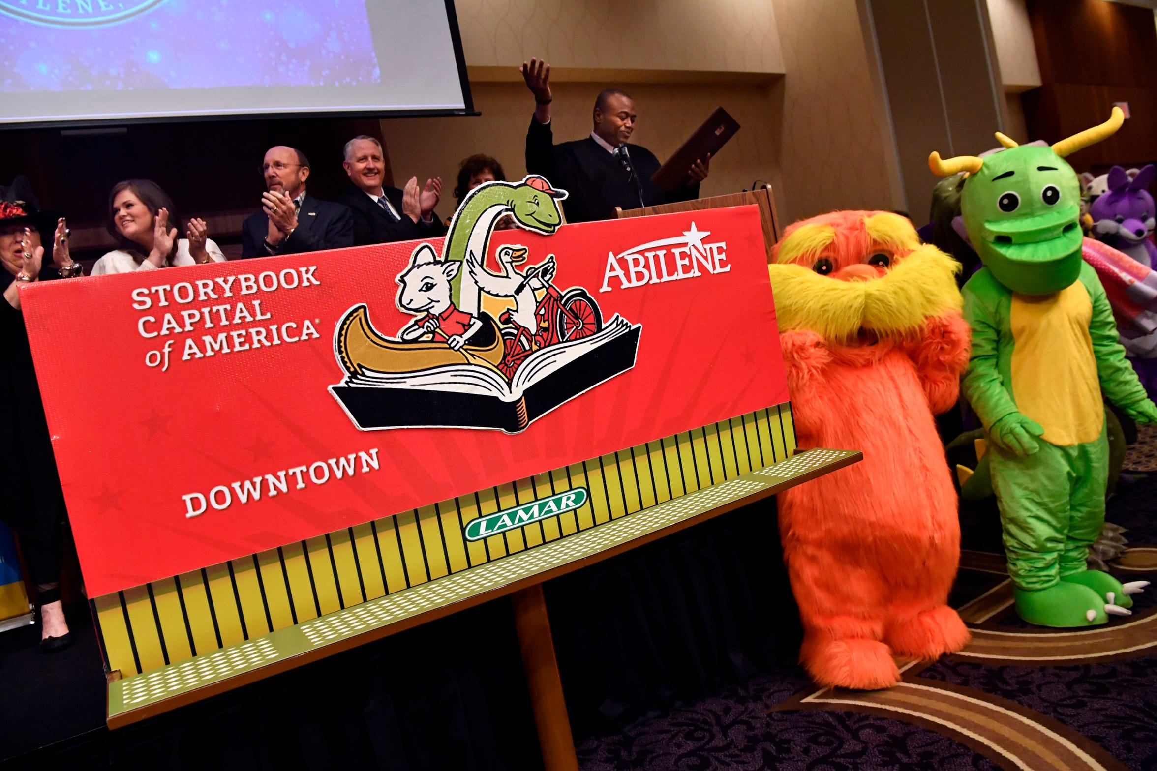 """Abilene Mayor Anthony Williams gestures for everyone at the """"Celebrate the Arts in Abilene"""" luncheon to stand after unveiling a new billboard Oct. 17. The mayor read a proclamation declaring the city would now be known as the Storybook Capital of America, according to the United State Patent and Trademark Office."""