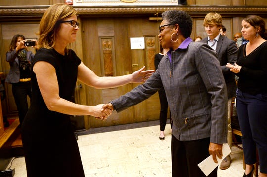 Asheville Mayor Esther Manheimer shakes hands with Debra Campbell after City Council unanimously approved her hiring as the city manager of Asheville.