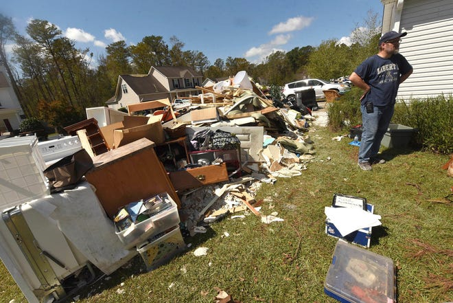 Brian Morris looks at the debris from his home in the Stoney Creek Plantation neighborhood in Leland in southeastern North Carolina in late September. Many of the homes here were flooded through their bottom floors due to rains from Hurricane Florence.