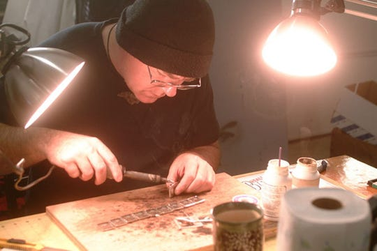 Lee Miller, one of the artists featured in the upcoming Art by the Tracks, works on his handcrafted jewelry in his studio.