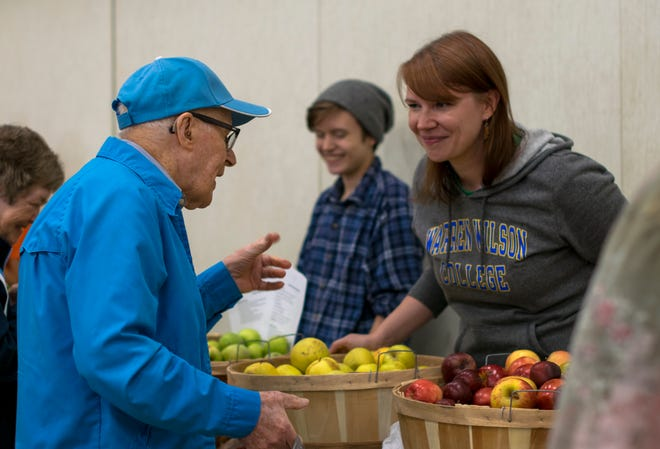 A Bounty & Soul volunteer helps a man as he passes through the line at a Tuesday market at St. James Episcopal Church in Black Mountain.