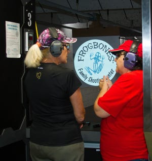 Luann Moyer, right, works with Mari Hiltz at Frogbones Family Shooting Center in Melbourne.