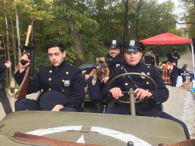 """Colchester police Cpl. David Dewey, center, and K9 Tazor pose with two other actors on the set of """"Rest"""" earlier in October. Dewey and Tazor play a guard and guard-dog in the short film."""
