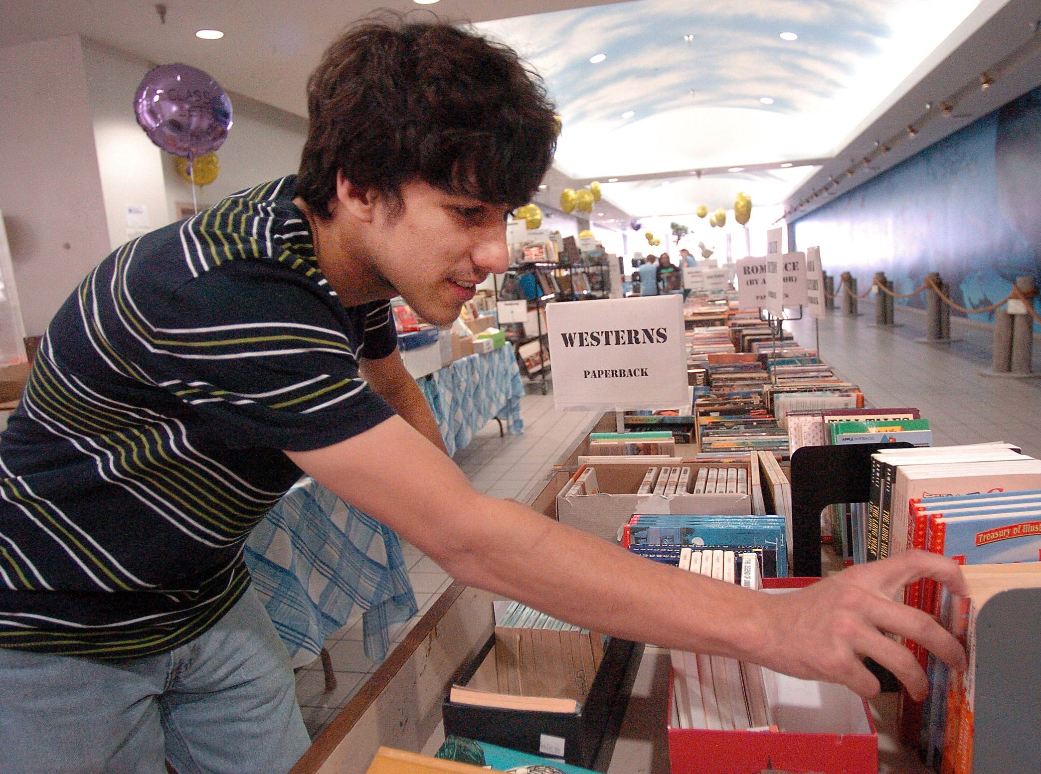 Reece Bowers buys books from the Brandeis Book Sale at Sunrise Mall in March 2014.