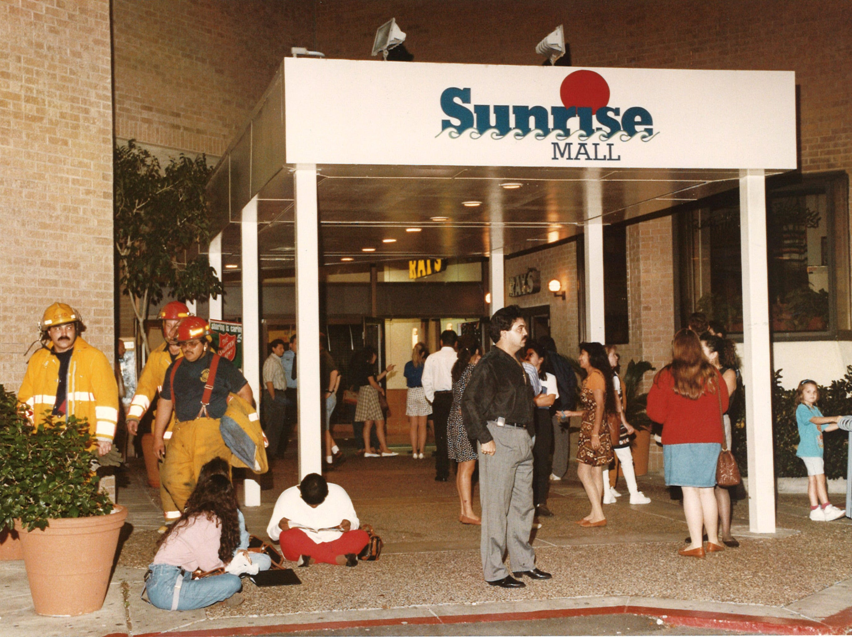 Firefighters from Fire Station No. 7 (at left) exit Sunrise Mall next to Ray's Restaurant as a crowd who evacuated earlier waits for the all-clear on Dec. 21, 1994.