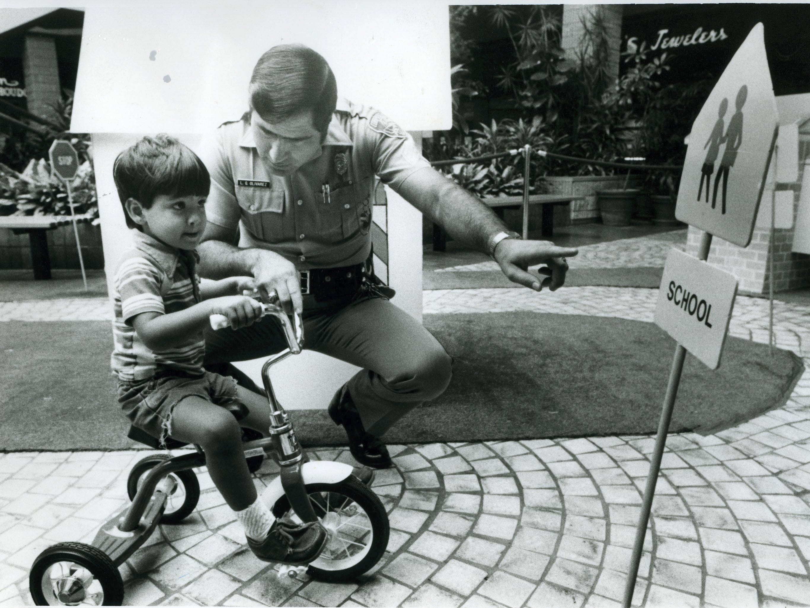 Paul Michael Uribe, 3, drives his tricycle through Safety City at Sunrise Mall in September 1982. Officer Larry Olivarez leads the children through the course and issues them a certificate upon completion of their drive.