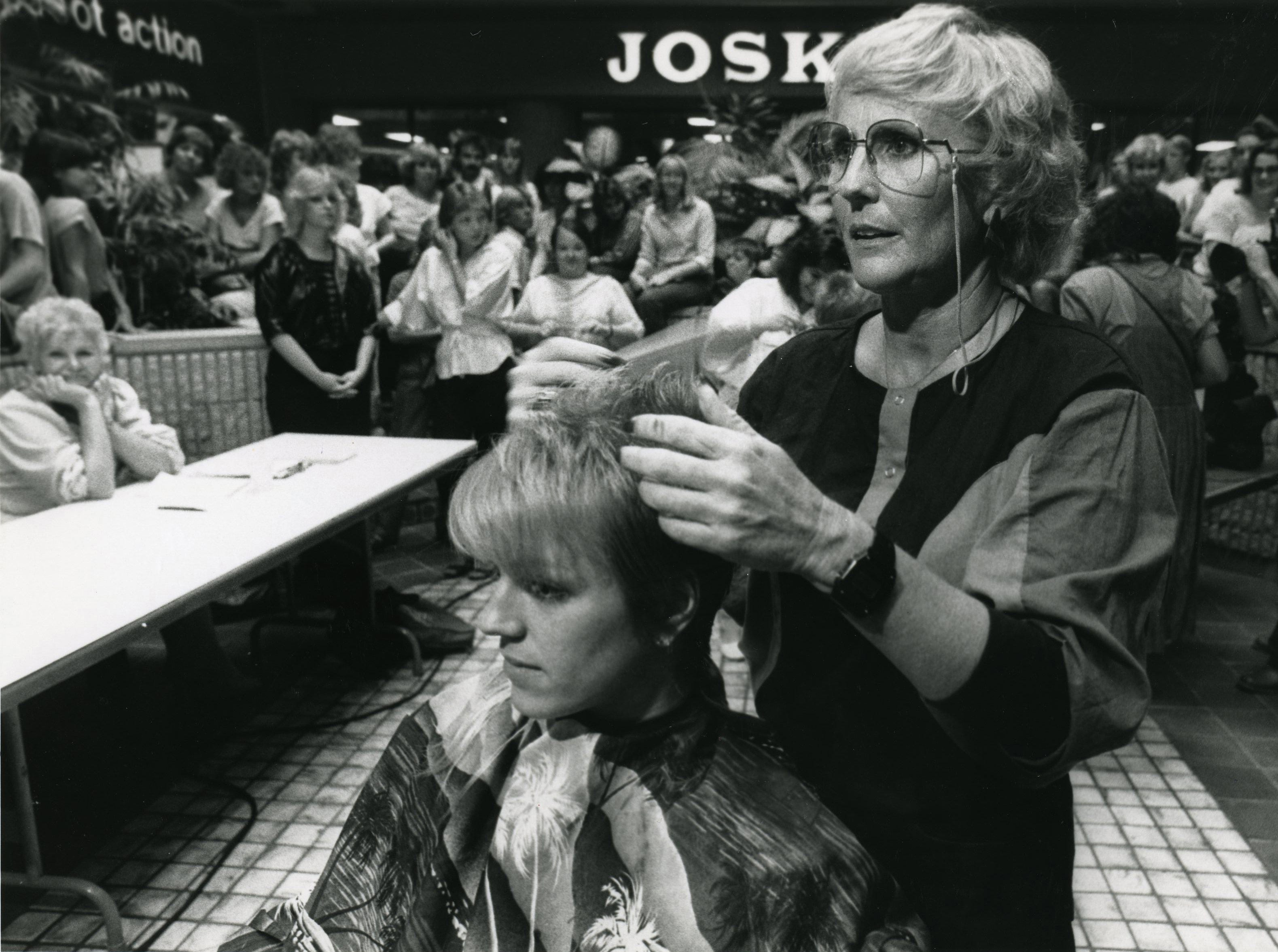 "C-101 DJ Bonnie Stacy was one of the first to get her hair cut by Hollywood stylist Lynn Del Kail at Sunrise Mall for the Tri-Star Production of ""The Legend of Billie Jean"" on Oct. 16, 1984. Extras in the background waited their turn to get the haircut."