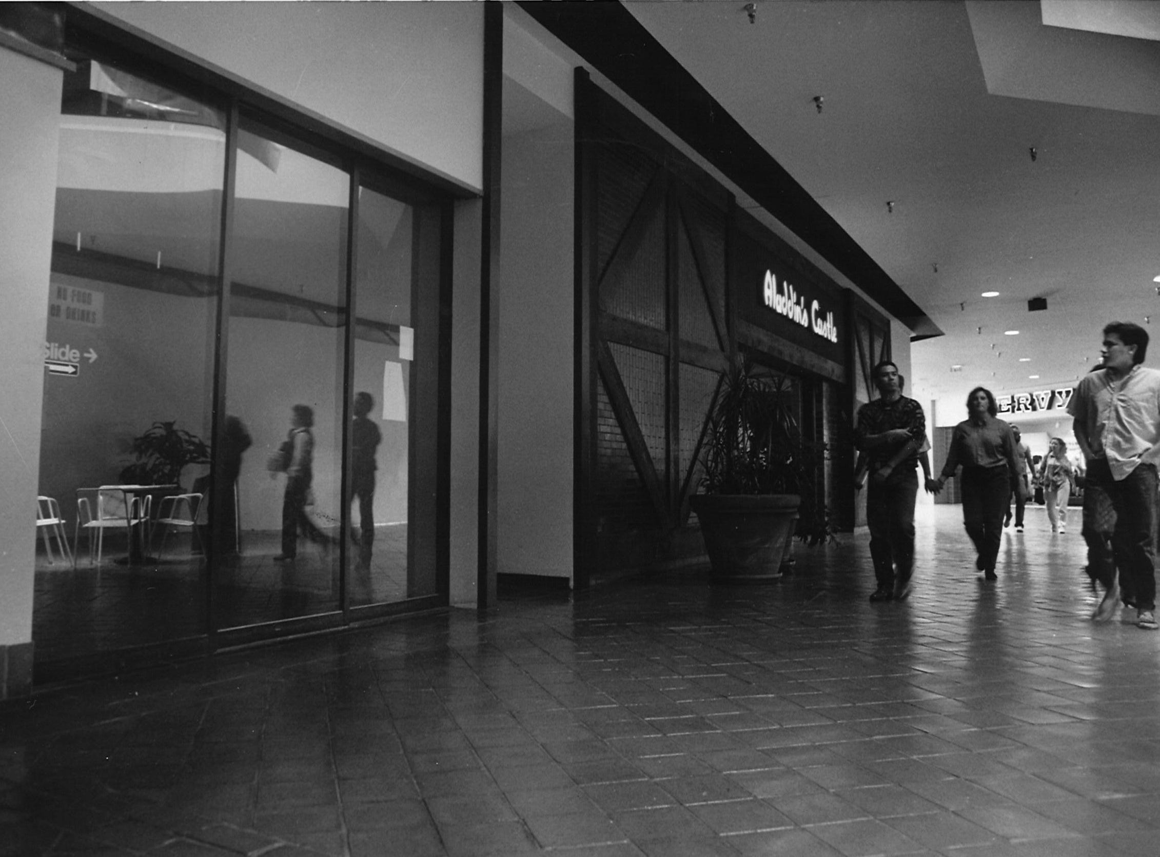 Shoppers at Sunrise Mall walk past the future location of a Corpus Christi Police substation in between Aladdin's Castle and Zales Jewlers on Dec. 27, 1988.