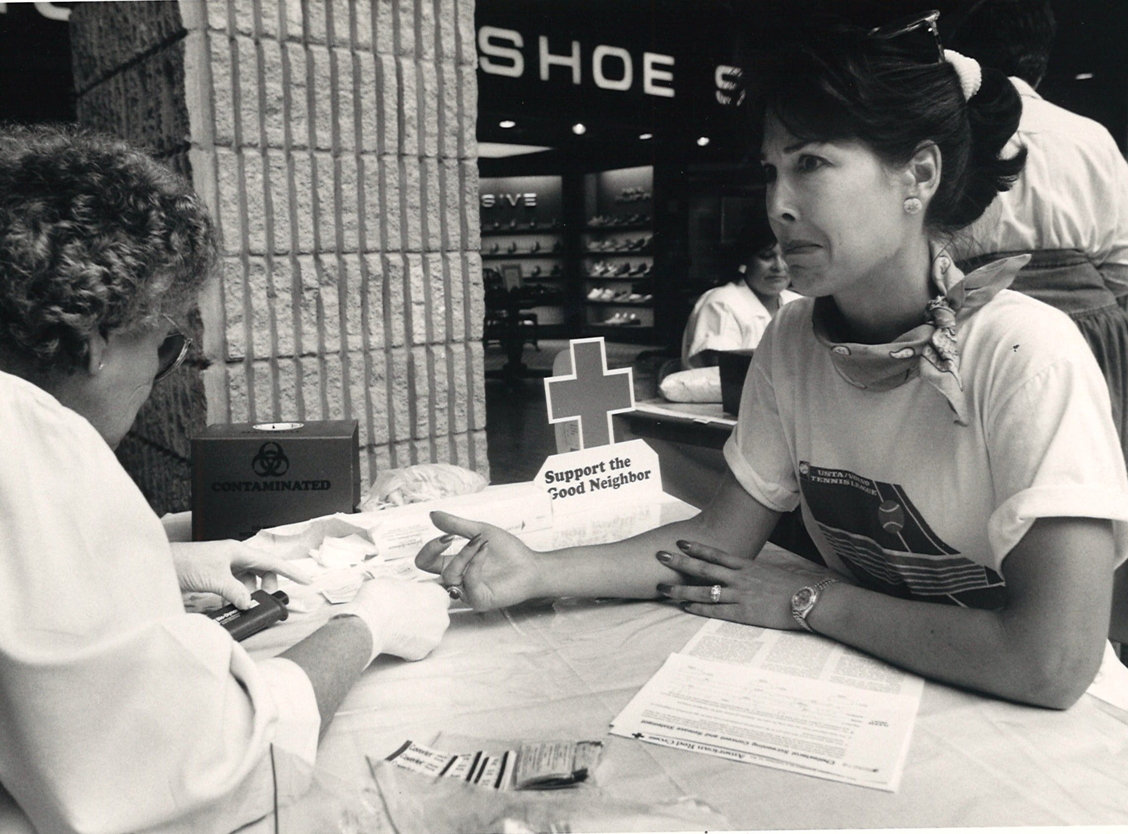 Grimacing at the prospect of having her finger speared by LNV Velma Atkins, Linda Herndon bites her lip waiting for the pain during $5 cholesterol testing at Sunrise Mall on Oct. 16, 1987.