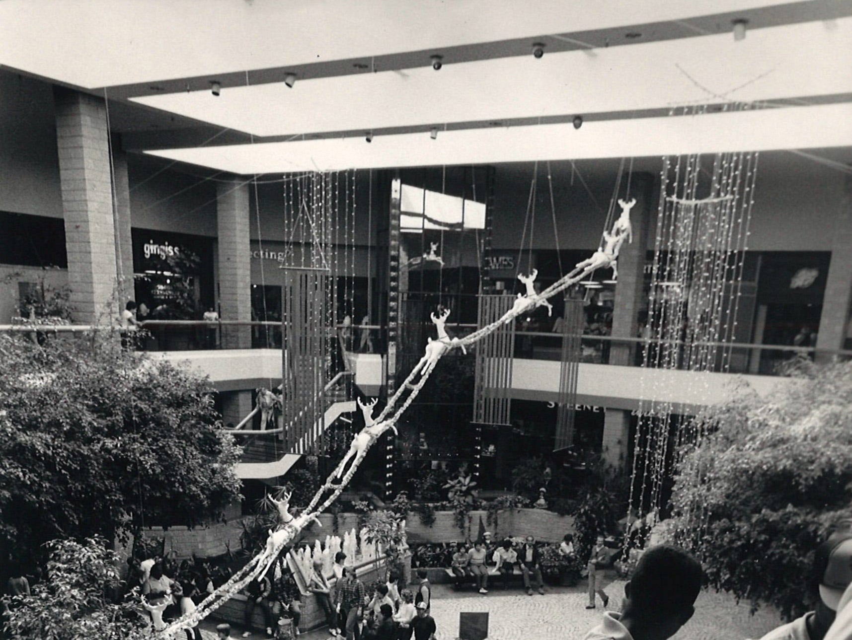 Shoppers take the escalators in the central atrium on Sunrise Mall on Nov. 23, 1984.