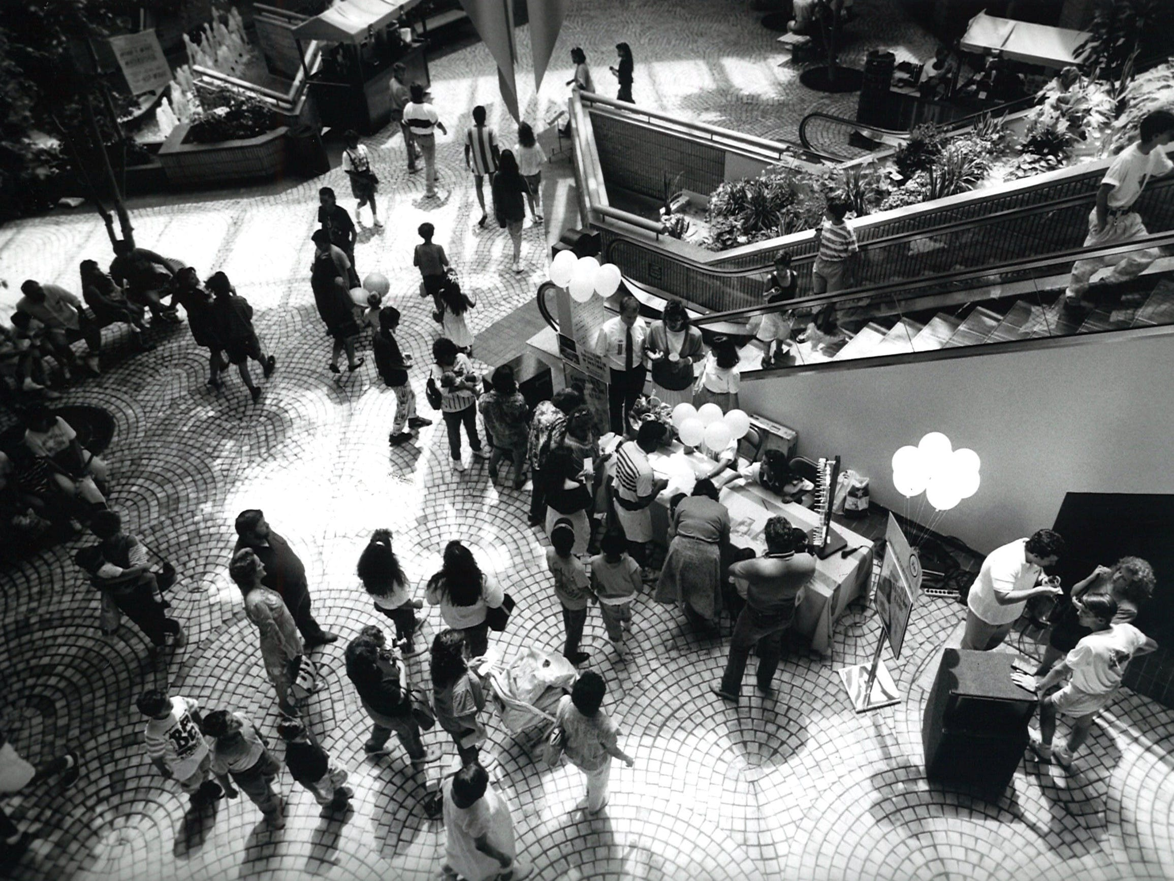 Shoppers stop at booths in the atrium of Sunrise Mall on July 17, 1990.