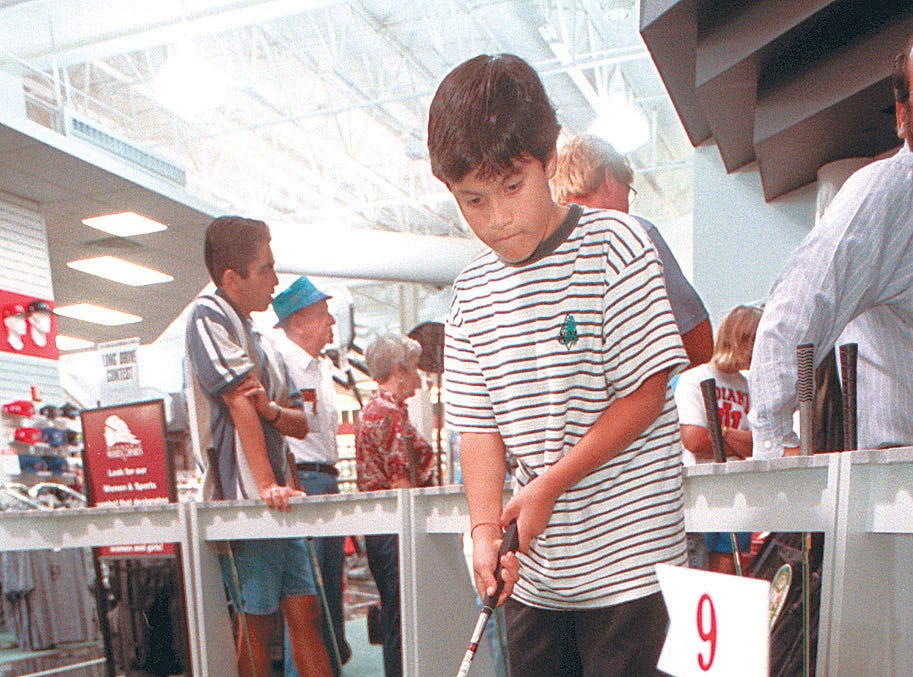 Ten-year-old Charlie Brown plays around on the putting mat in the newly opened Oshman's SuperSports USA at Sunrise Mall Oct. 19, 1996. The mall features several areas where customers can try the equipment including a basketball court, and a batting cage.
