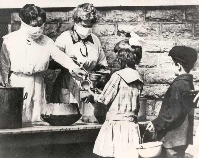 Volunteers wear gauze masks at a Cincinnati street kitchen while serving food to children of families afflicted by the worldwide Spanish influenza pandemic in 1918.