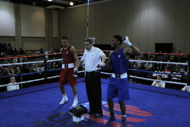 Lavars Carter, right, celebrates winning the 152-pound division at the Eastern Division USA Boxing Qualifier. He'll fight at the National Championships in December.