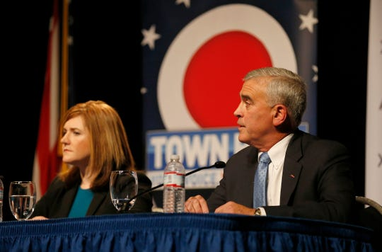 U.S. Rep. Brad Wenstrup answers a question as opponent Jill Schiller listens during a debate forum for the first and second congressional districts of Ohio hosted by AJC Cincinnati at the Mayerson Jewish Community Center in Amberly, Ohio, on Tuesday, Oct. 16, 2018.