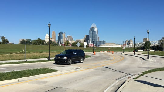 An SUV whirs south Wednesday on a new 1.4-mile extension of Ky. 9 through Newport. The extra lane at right is a parking lane protected by a median running for several city blocks.