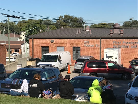 People lined up for lunch outside the Loaves & Fishes building at First Presbyterian's building at 215 Foster Street, on Oct. 17, 2018.