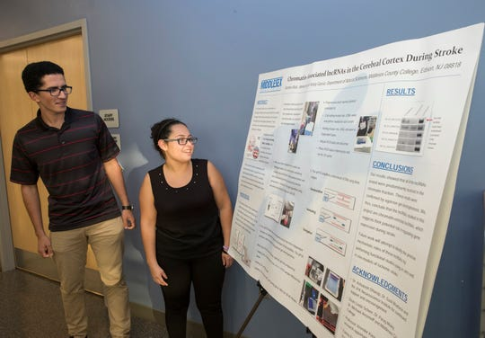 Ahmed Aly and Kristy Garcia  look at their poster explaining the results of their work.