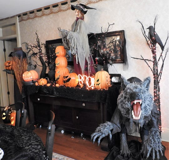 A werewolf and headless horseman figure are newer items part of a woodsy theme in Shelly Lillibridge's dining room. Each room gets a different theme each year.