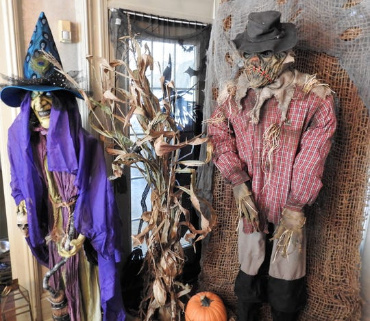 A witch and scarecrow are part of the Shelly Lillibridge's dining room which is decorated with a woodsy theme for Halloween.