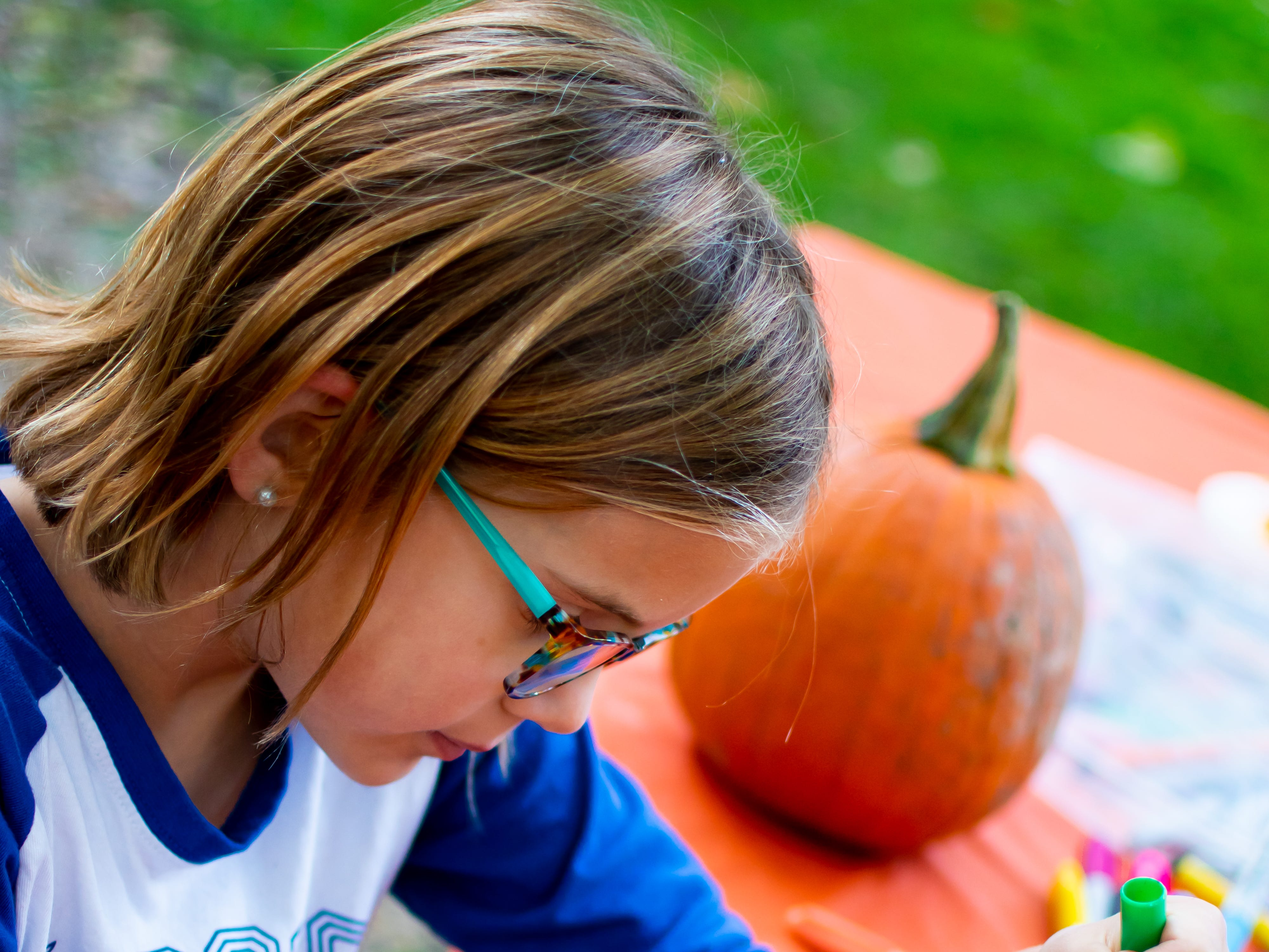 Olivia Berger, 7, of Urbandale, decorates a pumpkin on Tuesday, October 16, 2018 for the Waukee Area Chamber of Commerce fall after hours party at Timberline Campground in Waukee.
