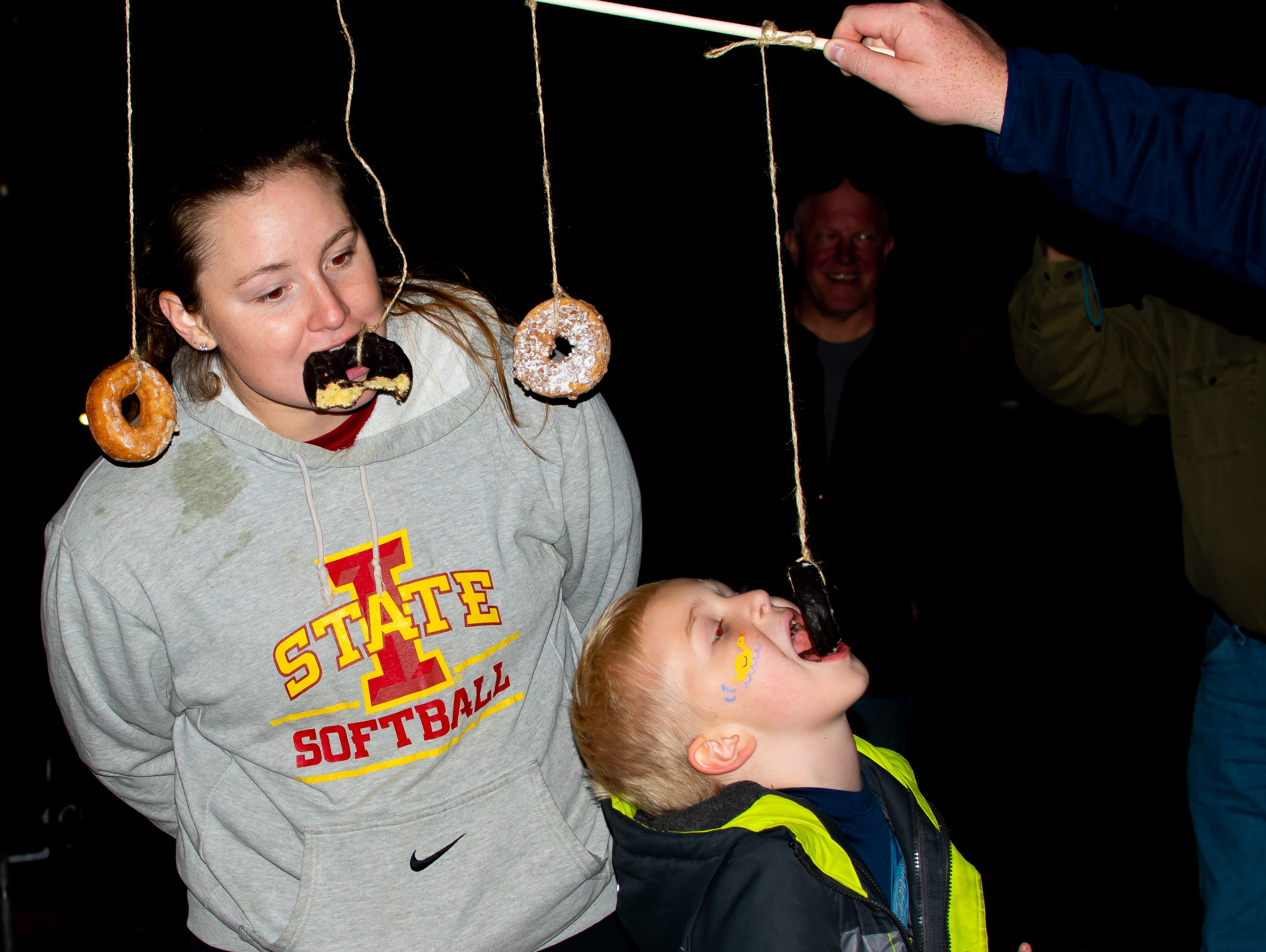 Sammie Hildreth, of Johnston, and Carson Budde, 6, of Windsor Heights, see who can eat donuts the fastest with no hands on Tuesday, Oct. 16, 2018 for the Waukee Area Chamber of Commerce fall after hours party at Timberline Campground in Waukee.