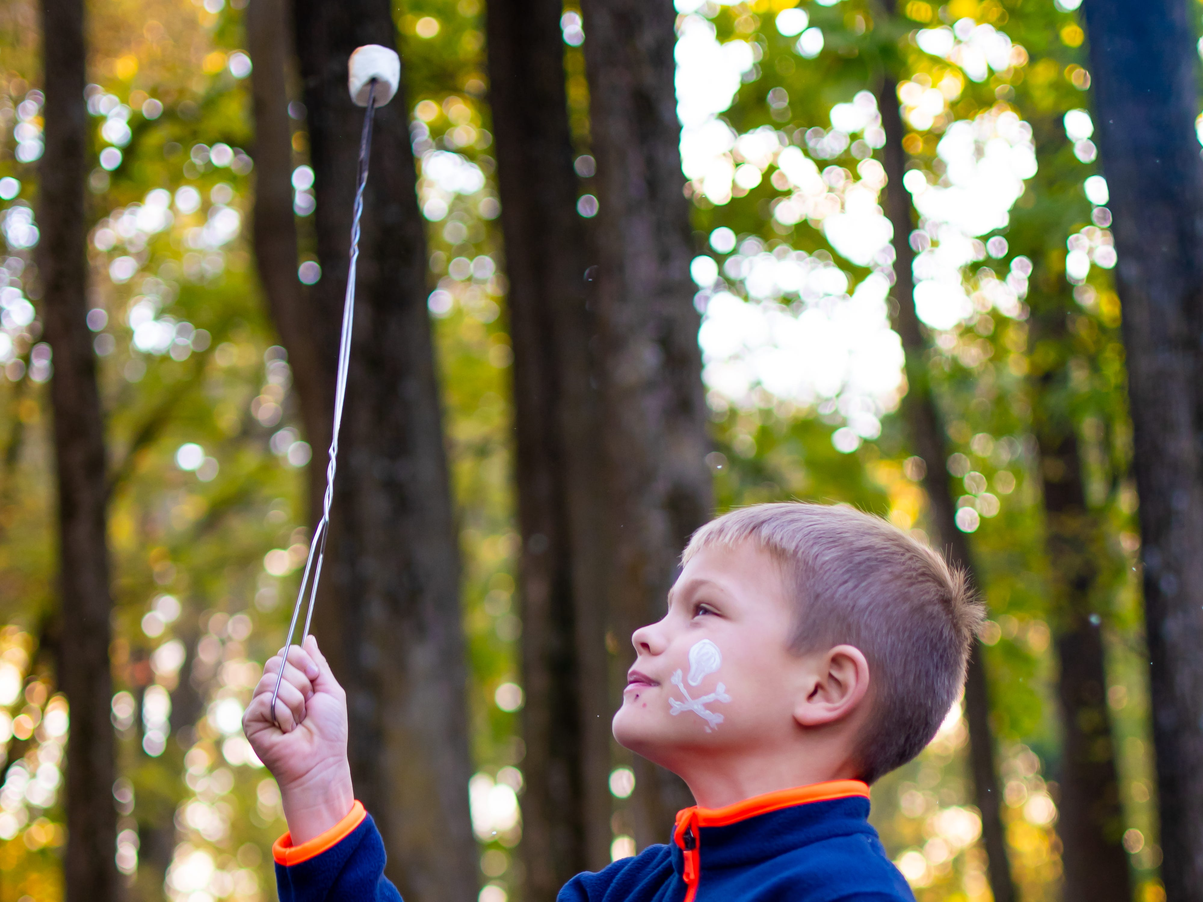 Jimmy Scott, 6, of Waukee inspects his marshmallow on Tuesday, Oct. 16, 2018 for the Waukee Area Chamber of Commerce fall after hours party at Timberline Campground in Waukee.