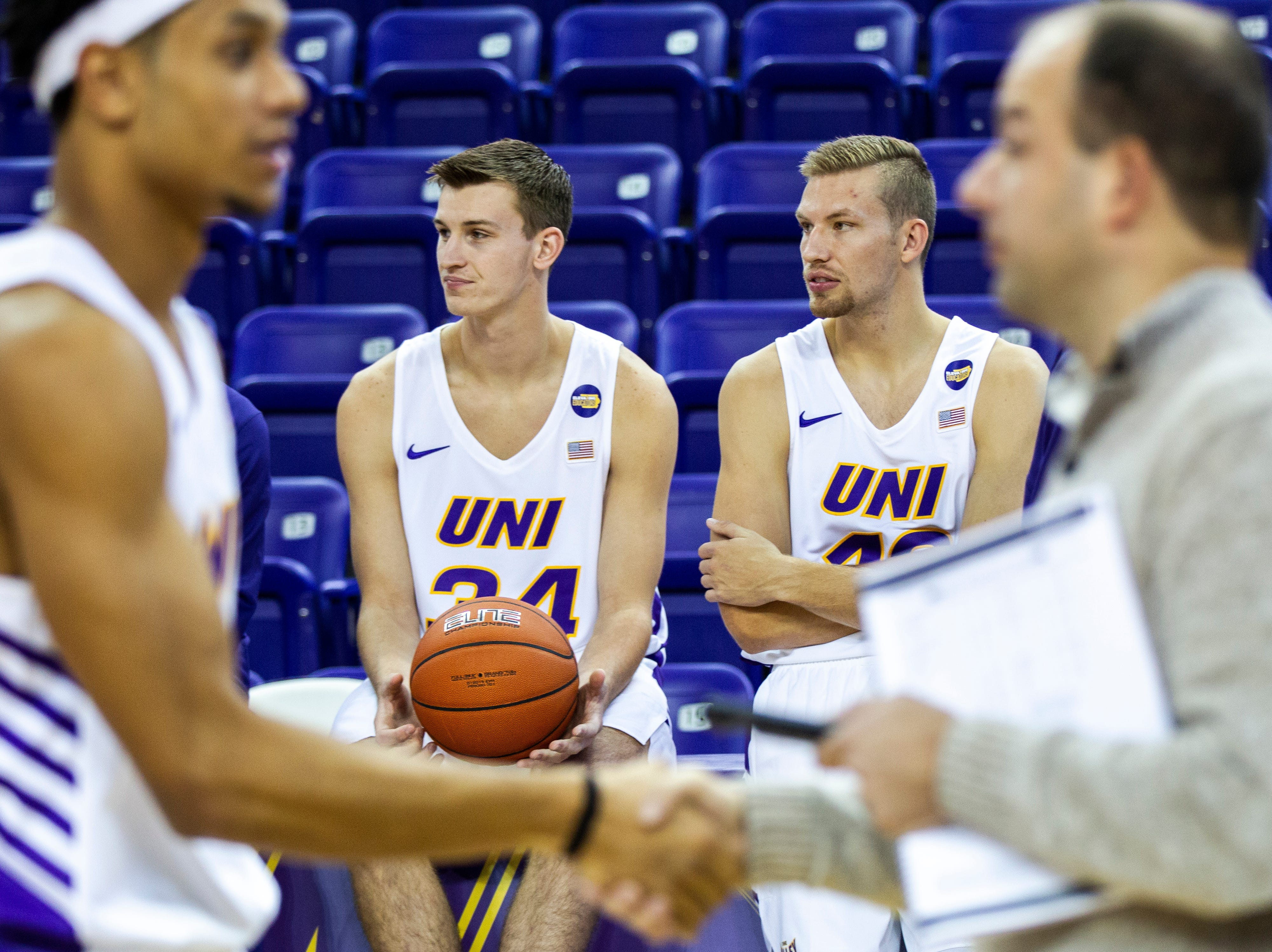 Northern Iowa forwards Luke McDonnell (34) and Lincoln Conrey (12) sit on the scorers table during Panthers men's basketball media day on Wednesday, Oct. 17, 2018, at the McLeod Center in Cedar Falls.