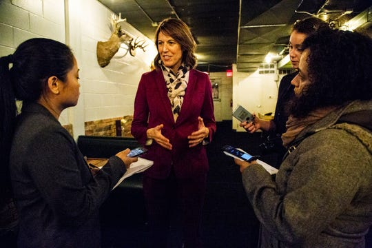 Cindy Axne, running against David Young to represent Iowa's third district, talks with reporters after an event at Reed's Hollow on Tuesday, Oct. 16, 2018, in Des Moines.