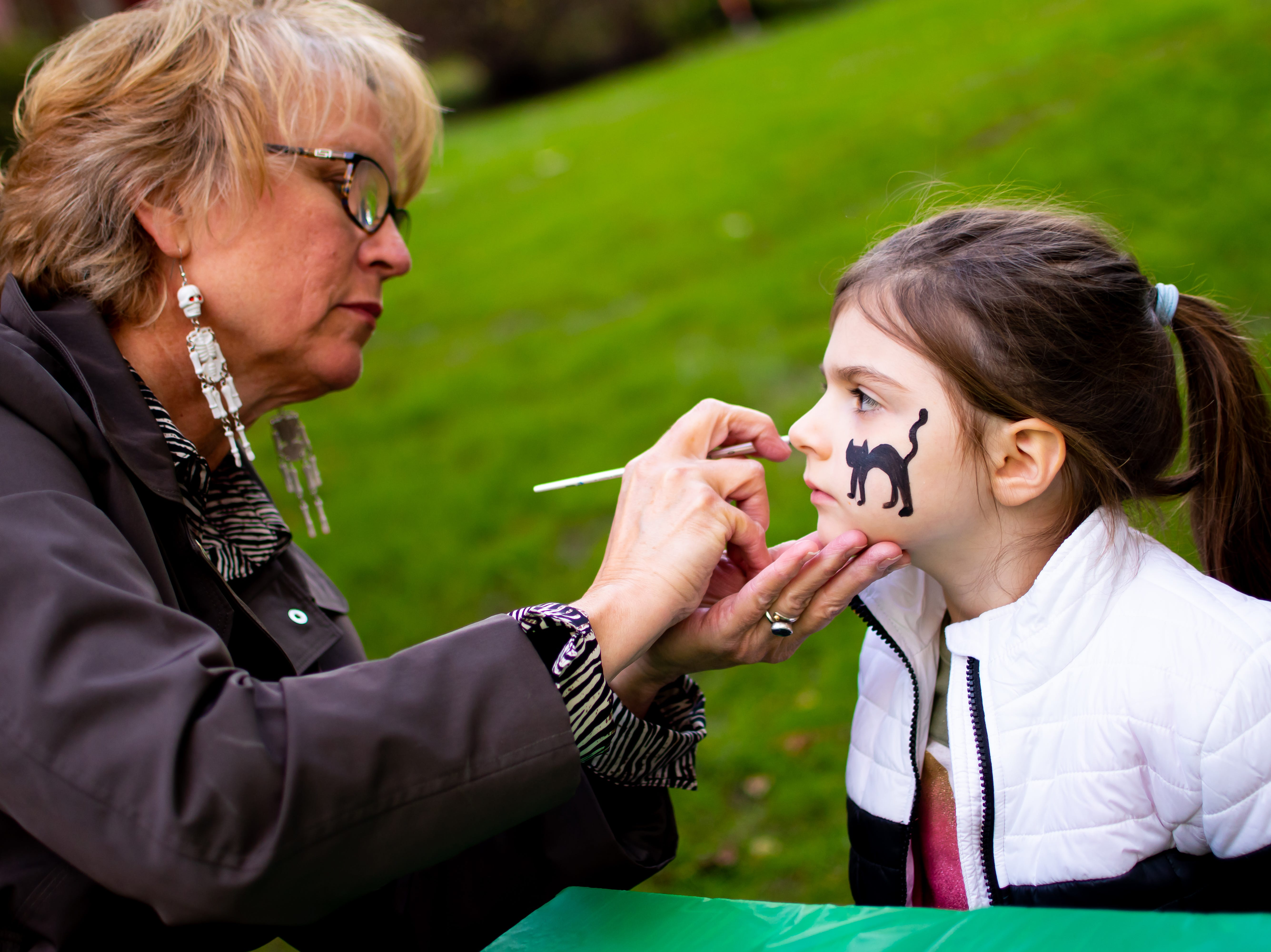 Chelsea Miller, 4, of Waukee gets her face painted  by Paula Nelson on Tuesday, Oct. 16, 2018 for the Waukee Area Chamber of Commerce fall after hours party at Timberline Campground in Waukee.