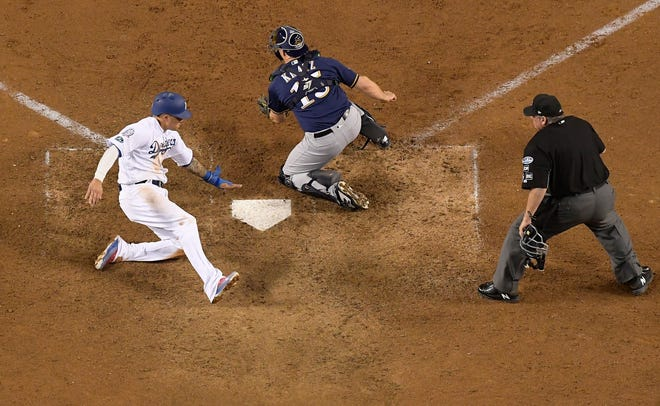 Los Angeles Dodgers' Manny Machado scores past Milwaukee Brewers catcher Erik Kratz during the 13th inning of Game 4.